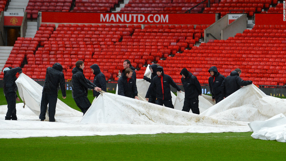 The match was cleared to go ahead after a late pitch inspection following days of rain in the UK. Groundstaff remove waterproof covers which protected the playing surface.