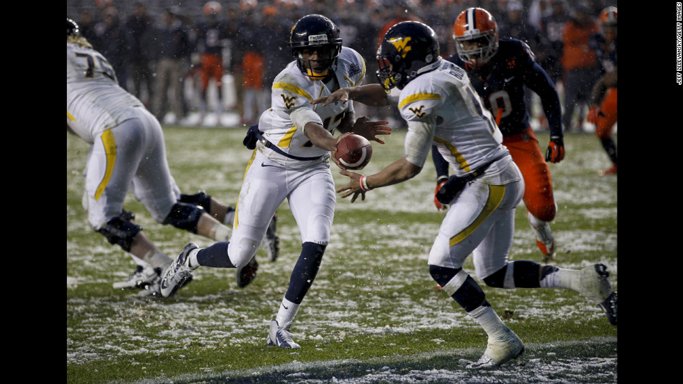 Geno Smith, left, hands off to Andrew Buie of the West Virginia Mountaineers in the New Era Pinstripe Bowl against the Syracuse Orange at Yankee Stadium on December 29 in the Bronx, New York.