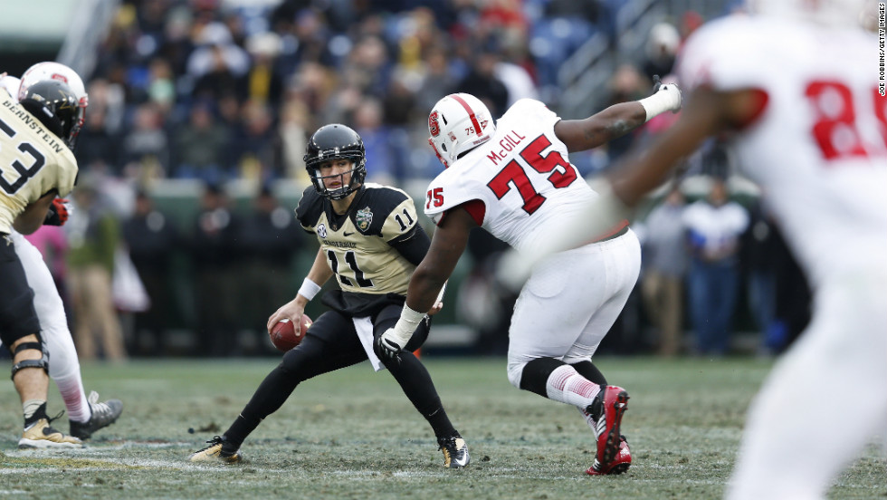 Jordan Rodgers of the Vanderbilt Commodores looks to pass the ball while under pressure from T.Y. McGill of the North Carolina State Wolfpack on December 31.