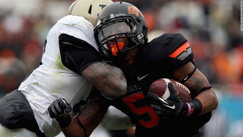 Josh Stewart of the Oklahoma State Cowboys is tackled by Josh Johnson of the Purdue Boilermakers on January 1