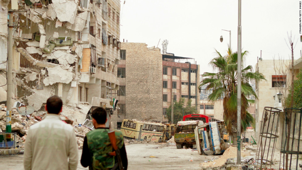 Rebel fighters inspect the debris on a street in the Bustan al-Basha district in the Syrian city of Aleppo on Tuesday, January 1.