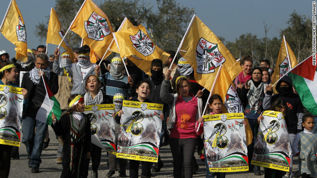 Palestinian protesters carry Fatah party flags during a march organised by residents of the West Bank village Nabi Saleh.