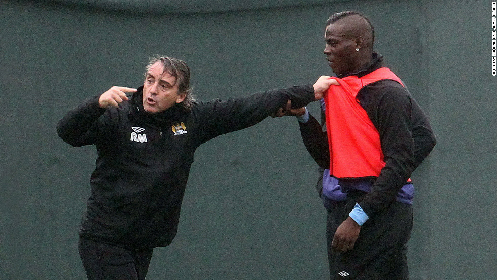 "Manchester City manager Roberto Mancini was photographed grappling with his firebrand striker Mario Balotelli during a training run on Thursday, prompting coaching staff to intervene to separate the pair. Mancini later downplayed the tussle, sparked by Balotelli's hostile tackle on a fellow player, as ""nothing unusual."""