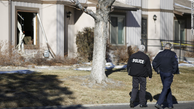 Aurora, Colorado Police walk by the scene where four people were killed Saturday morning including the gunman who held police at bay for several hours at the complex.