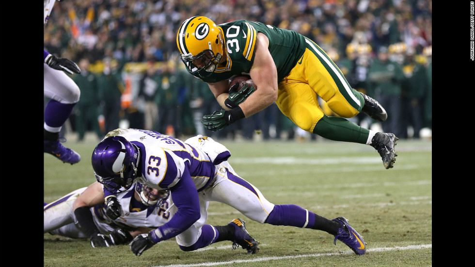 John Kuhn sails over Vikings safety Jamarca Sanford to score on a nine-yard touchdown catch and run.