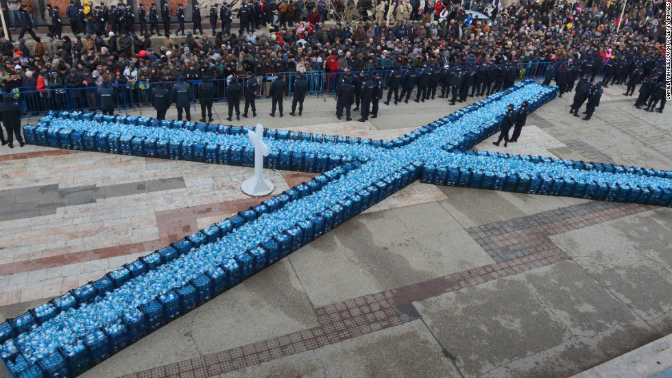 Romanian officers guard bottles containing holy water to be distributed after the service in Constanta City on Sunday.