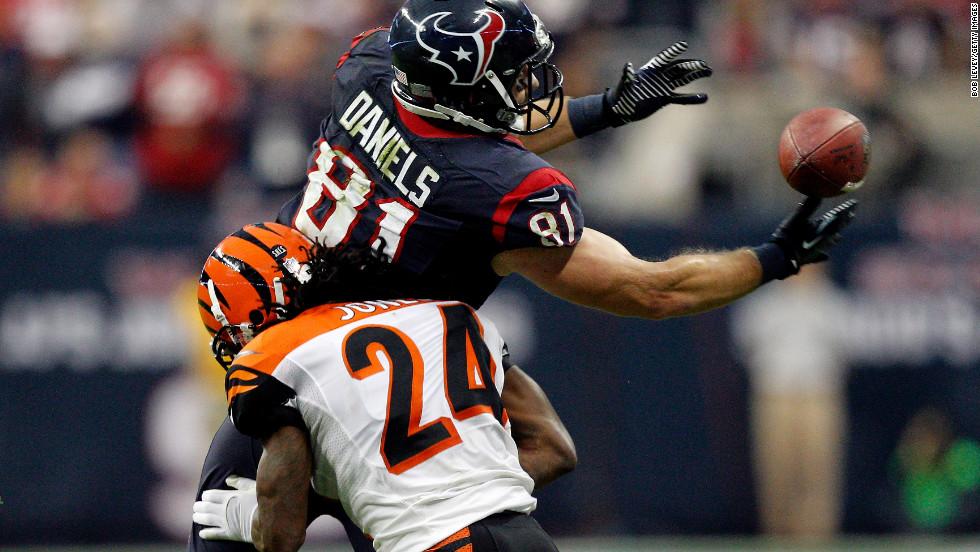 The ball slips through Owen Daniels' fingers as he is hit by Cincinnati's Adam Jones.