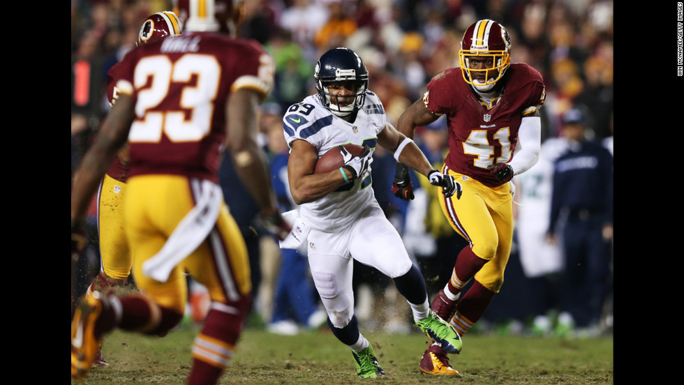Clinton McDonald of the Seattle Seahawks carries the ball against the defense of  DeAngelo Hall, left, and Madieu Williams, right, of the Washington Redskins on Sunday.