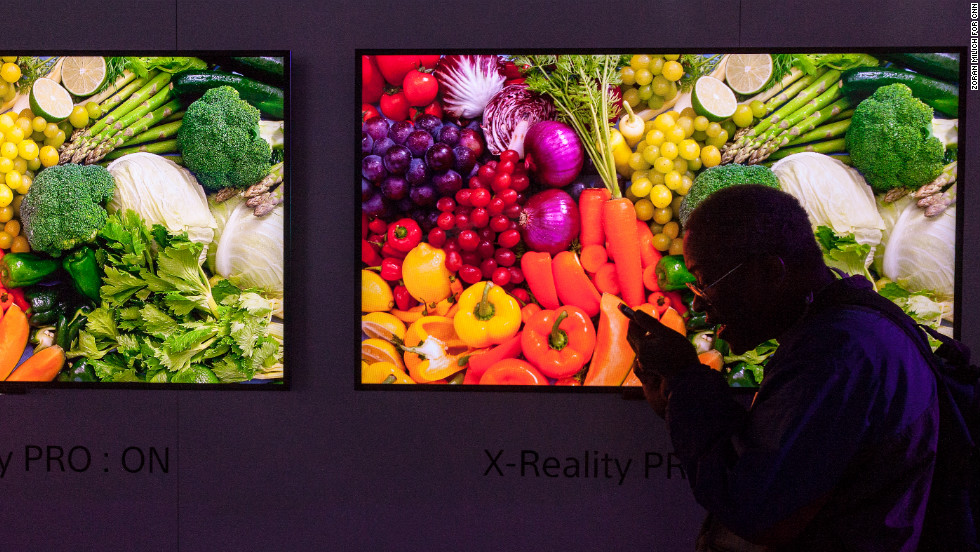 A man talks to his phone with Sony Bravia W900 LED LCD HDTV televisions in the background during Press Day at the Consumers Electronic Show on Monday.<br />