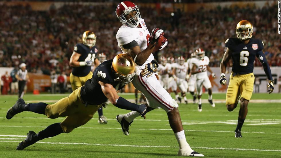 Zeke Motta of Notre Dame tackles Alabama's Amari Cooper.