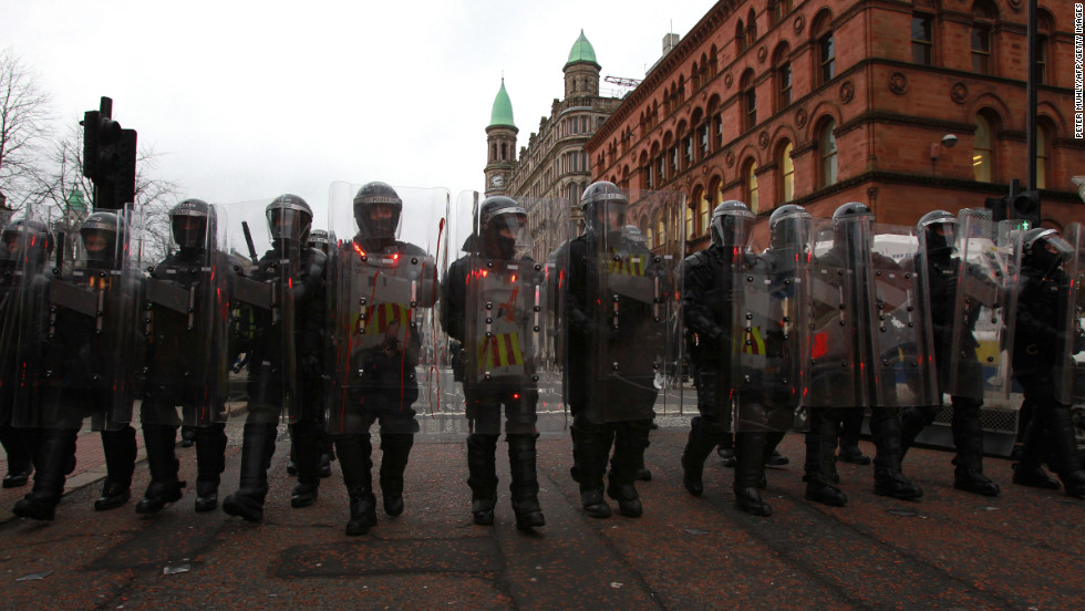 Police in riot gear march behind loyalist protesters on Saturday.