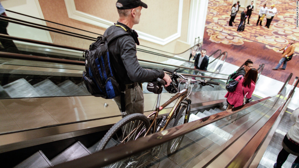 A man takes his bike down an escalator Monday at the Las Vegas Convention Center.