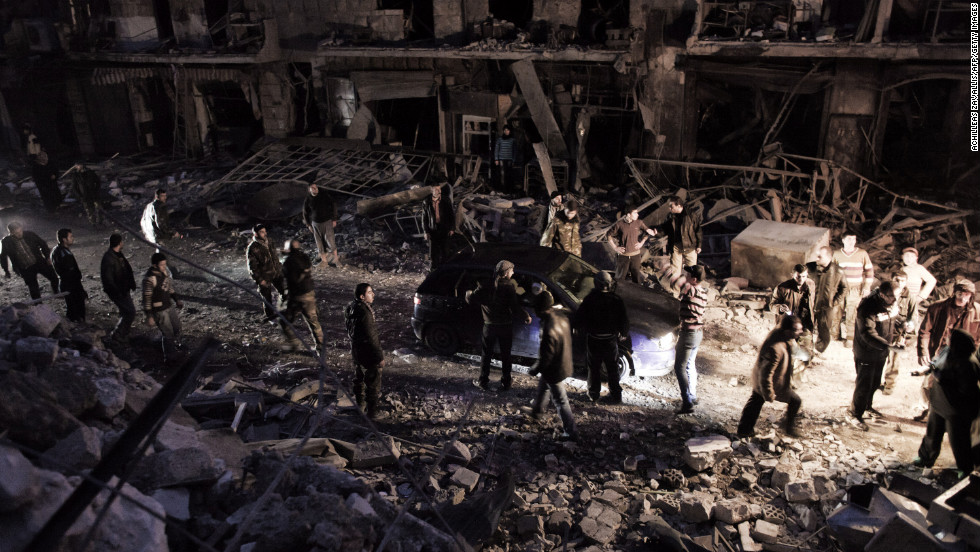 Syrians walk through debris in Aleppo after a missile hit a building January 7.