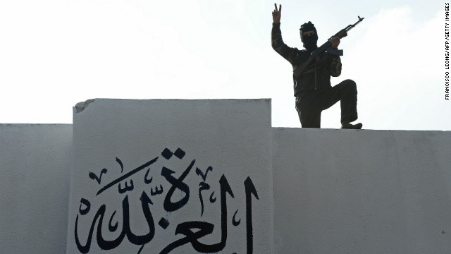 A Syrian member of the Committee for Promotion of Virtues and Prevention of Vice gestures near a freshly painted wall reading 'Glory to God' at their headquarters in al-Bab, northern Syria, on November 21, 2012. The committee was created to fight abuses and crimes committed by members of the Free Syrian Army (FSA) only, and has 80 elements recruited outside the FSA. The rebels faced growing criticism, particularly after a video was posted on YouTube earlier in November, appearing to show opposition fighters beating and executing soldiers after attacks