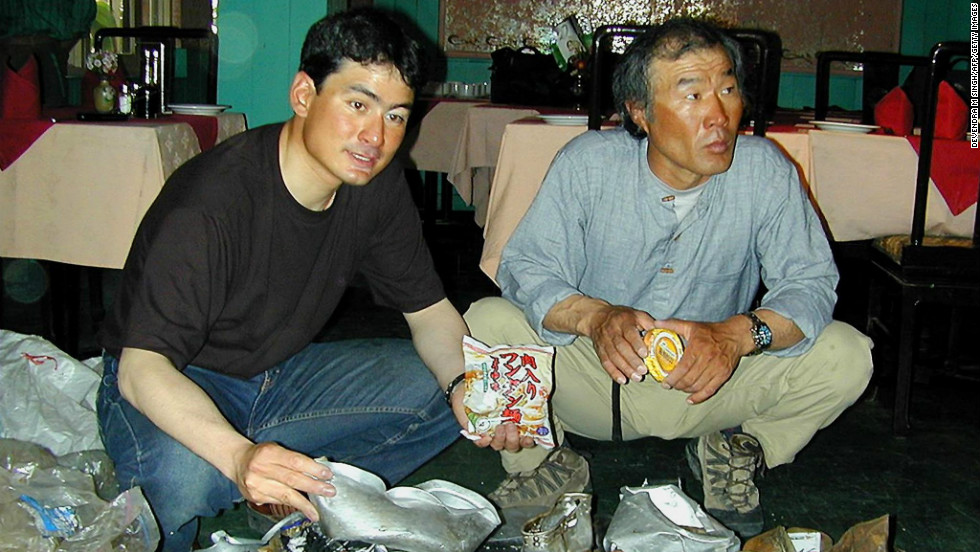 In this photograph taken in May 2001, Japanese mountaineer Ken Noguchi (L) and South Korean mountaineer Lee Sang-Bae (R) display  garbage collected from Mt. Everest during their cleaning expedition. They had brought back more than 1.7 tons of garbage from the trip.
