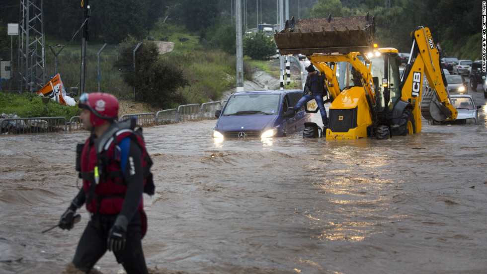 Rescue team evacuates people trapped in their cars in a flooded road near the Israeli-Arab town of Kfar Qara, in central Israel.