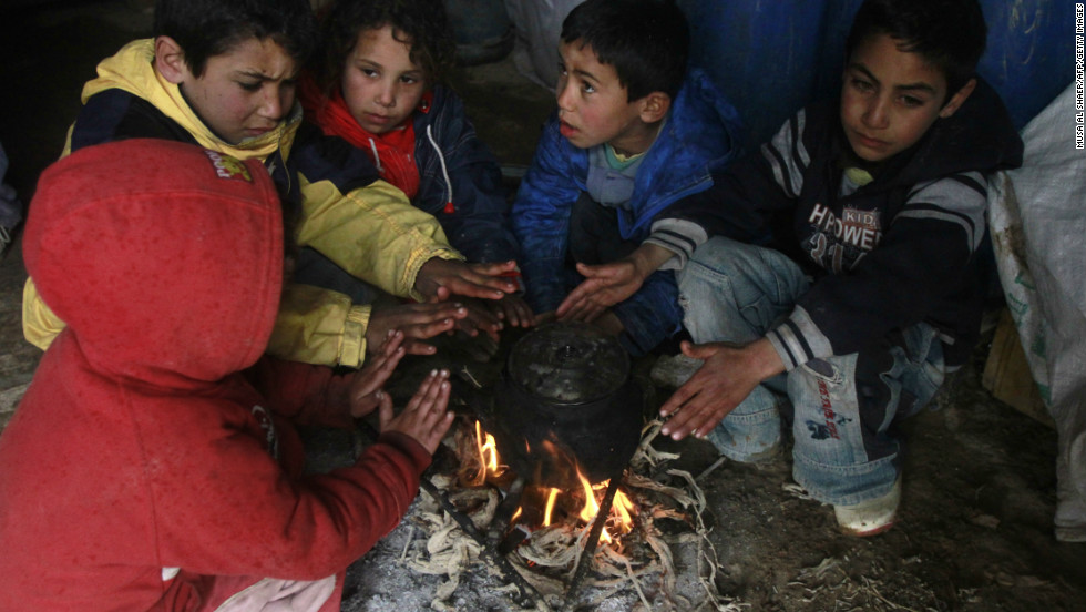 Bedouin children from the al-Rashaida tribe warm themselves by a fire under a tent at their camp south of the West Bank city of Bethlehem on January 8, 2013.