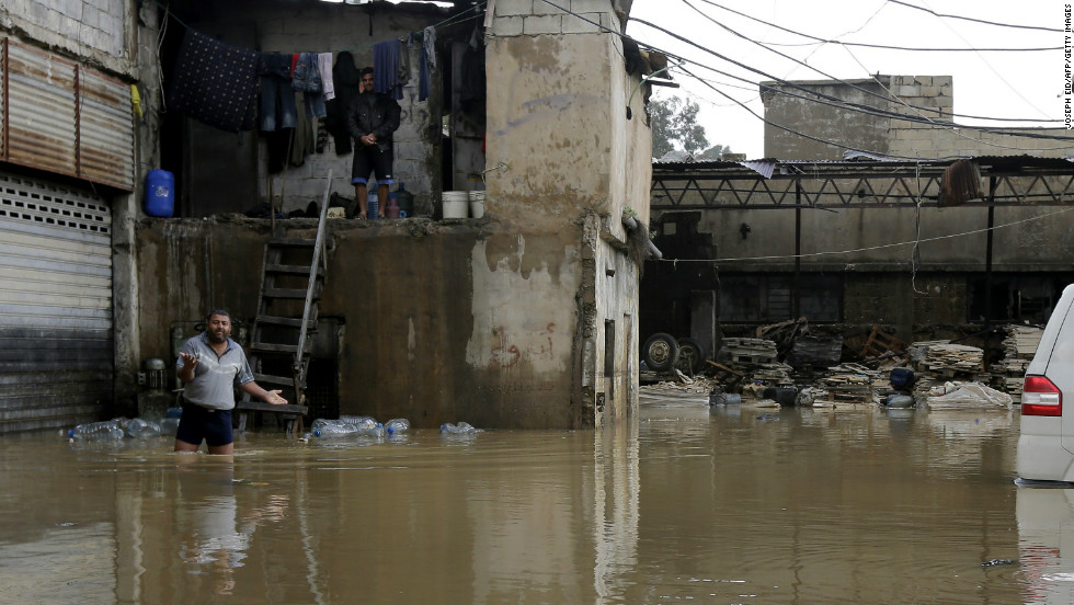 A man walks in a flooded yard as he comes out of his squat in the Lebanese capital Beirut, on January 7.