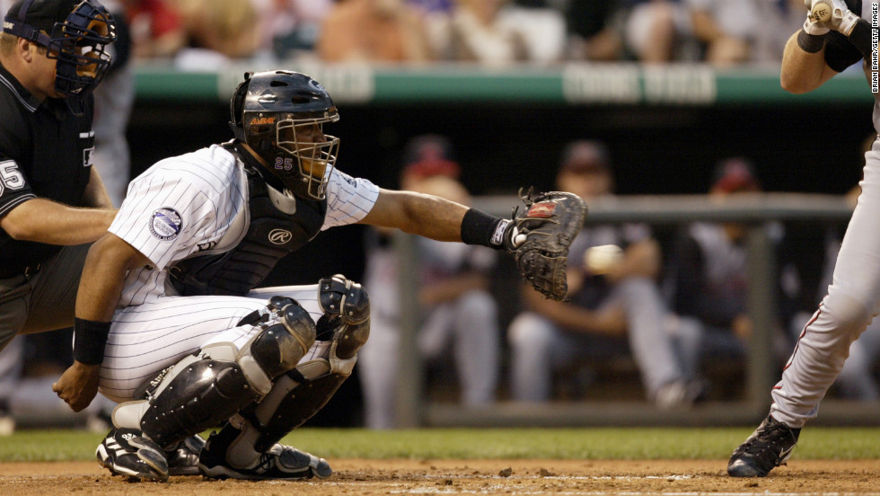 Sandy Alomar Jr. of the Colorado Rockies catches a pitch during a 2002 game against the Cincinnati Reds in Denver.