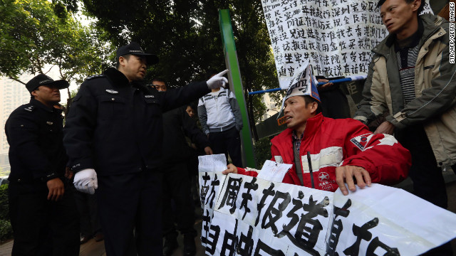 Protesters holding banners in support of greater media freedom confront police in Guangzhou on January 10.