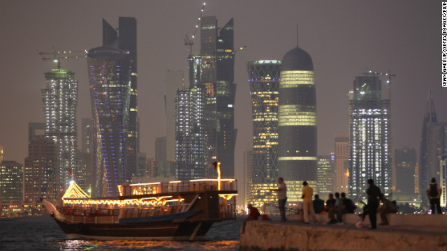 A boat arrives at a jetty in front of the sparkling Doha skyline.