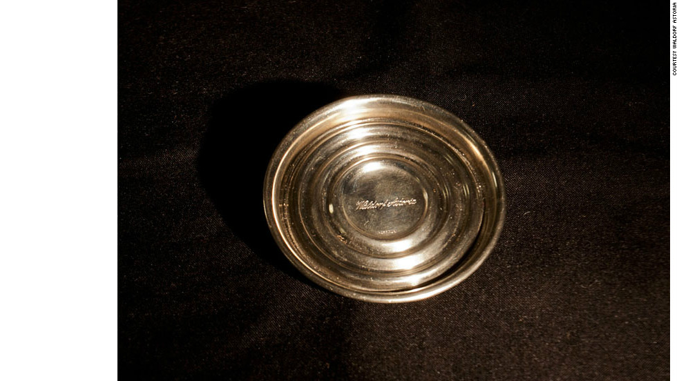A wine coaster thought to have been stolen from the Waldorf Astoria by a wealthy businessman in the 1950's. It is estimated the Waldorf served 60,000 bottles of wine a year during this period, with this metal device providing a valuable presentation service.