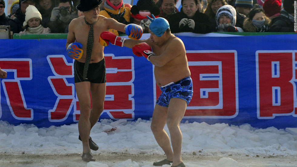 Winter swimming fans perform a boxing match on the frozen Songhua River during the Harbin festival, on Friday, January 11.