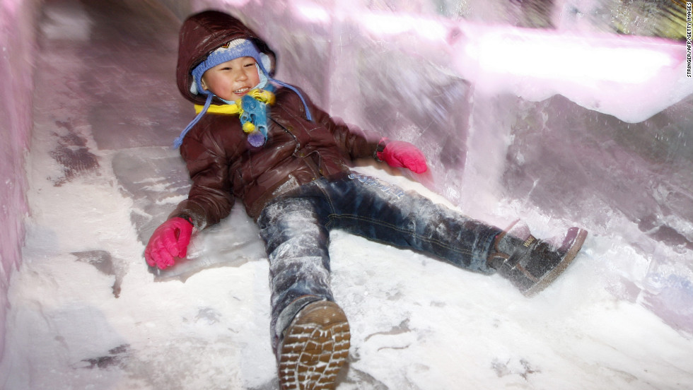 A young child slides down an ice slide at the opening ceremony of the Harbin festival on Saturday, January 5.