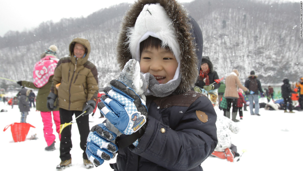 A child displays a fish caught during the ice fishing competition at the Hwacheon Sancheoneo festival.
