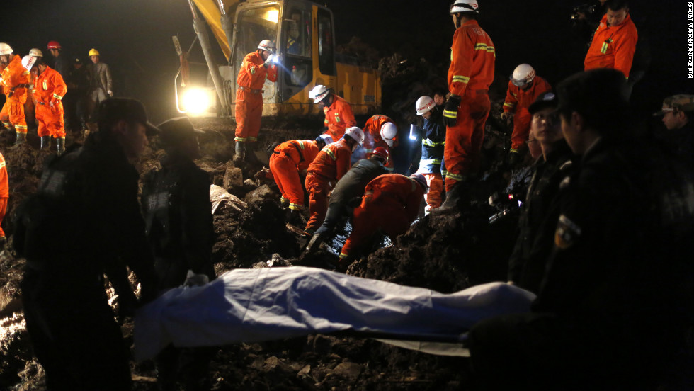 Rescuers carry a dead body from the area. The disaster prompted a massive search and rescue effort that included more than 20 excavators and front-end loaders.