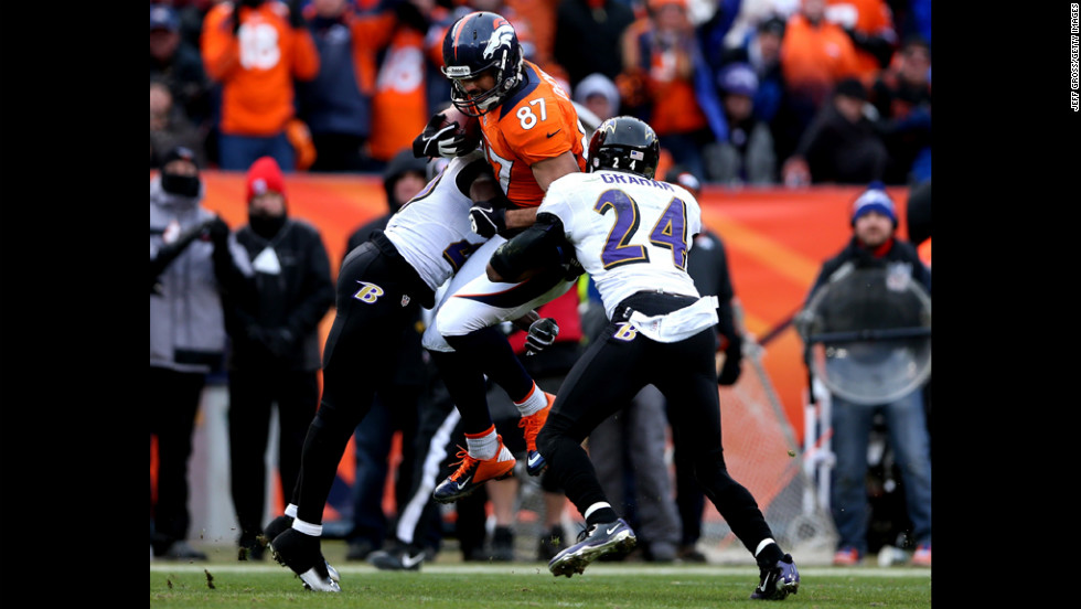 Eric Decker of the Broncos is tackled after making a reception in the second quarter against Ed Reed and Corey Graham of the Ravens.