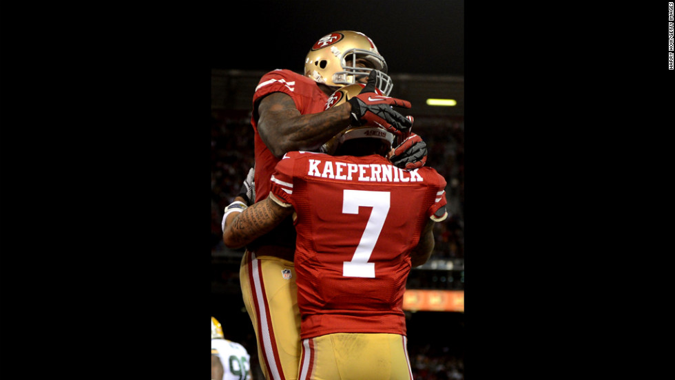 Quarterback Colin Kaepernick of the 49ers celebrates with a teammate after running in a touchdown in the first quarter against the Packers on Saturday.