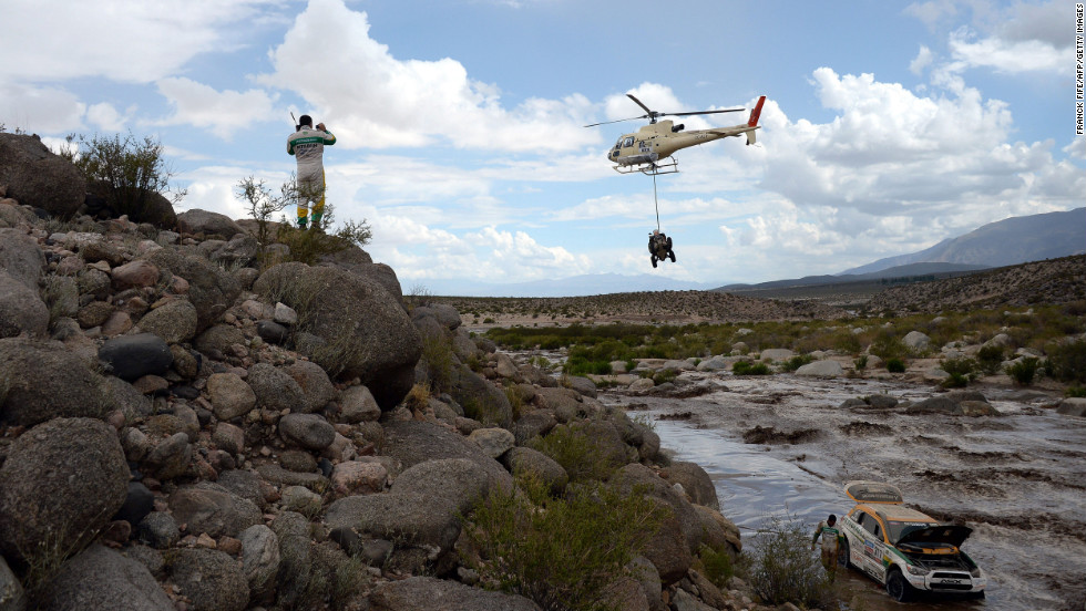 Brazil's Guilherme Spinelli looks down on his Mitsubishi stuck in a river below on January 12. Co-driver Youssef Haddad is next to the vehicle as a helicopter passes overhead with a bike.