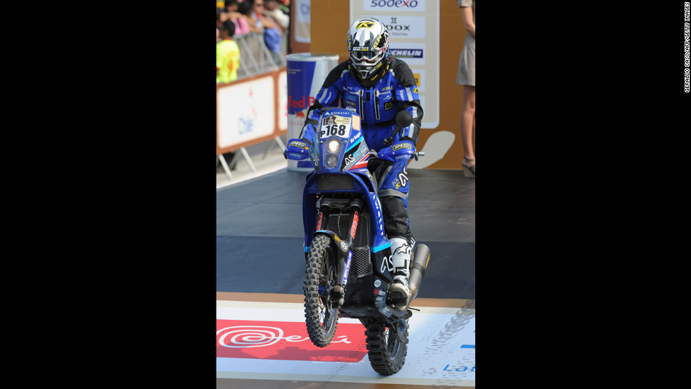 Great Britain's Lyndon Poskitt pops a wheelie on his KTM on January 5 during the departure ceremony.