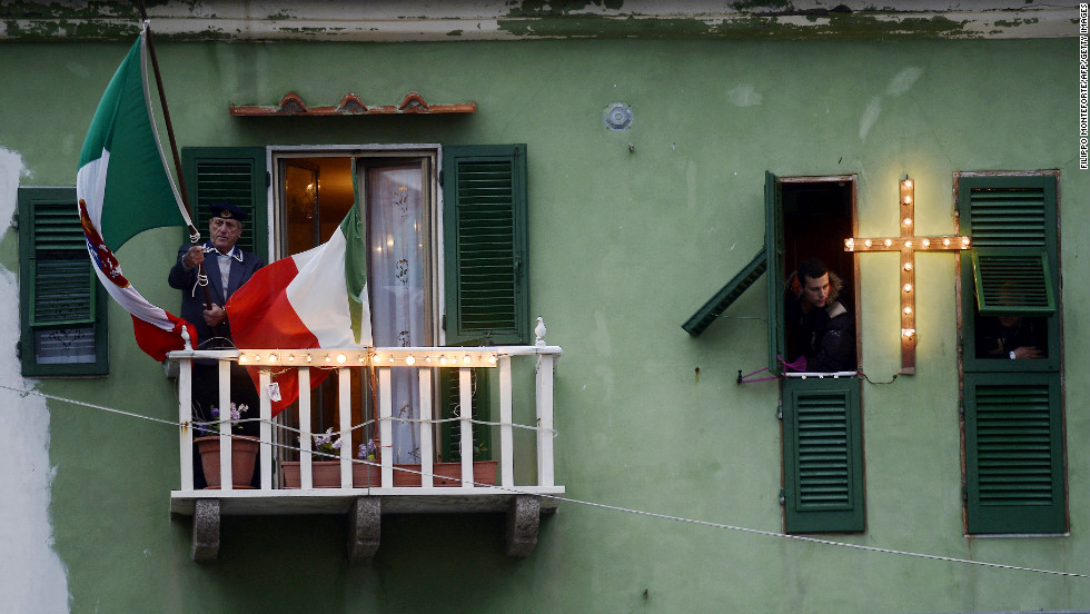 A man holds a flag on his balcony overlooking the port on the Italian island of Giglio on Sunday.