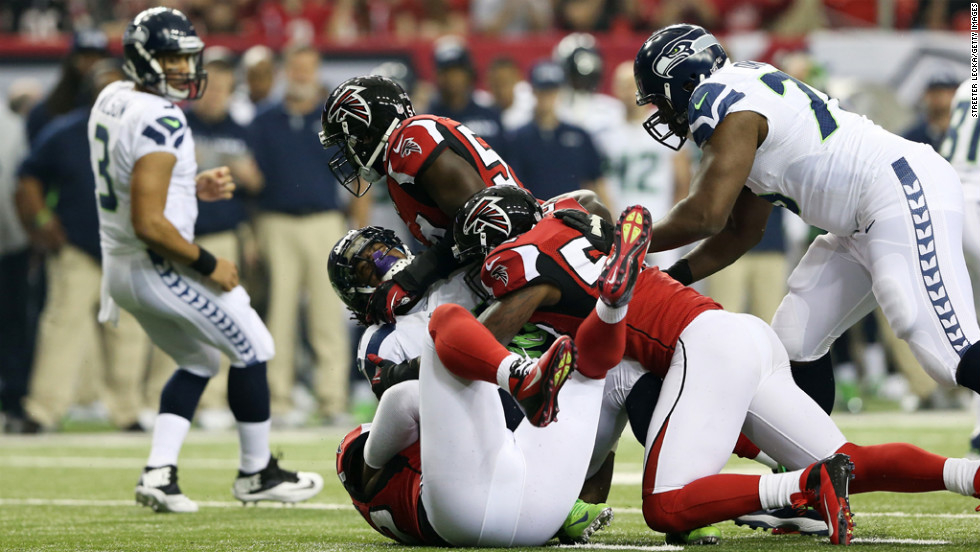 Akeem Dent and Stephen Nicholas of the Falcons tackle Marshawn Lynch of the Seahawks in the first quarter on Sunday.