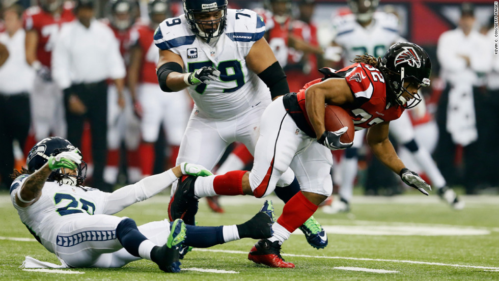 Jacquizz Rodgers of the Falcons breaks the tackle of Seattle's Red Bryant and gets past Earl Thomas on Sunday.