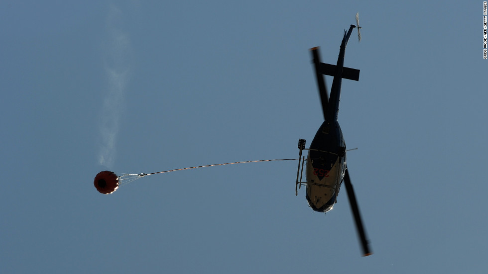 A water-bombing helicopter returns from a fire area to the town of Yass, in the southern part of New South Wales state, on Friday, January 11.