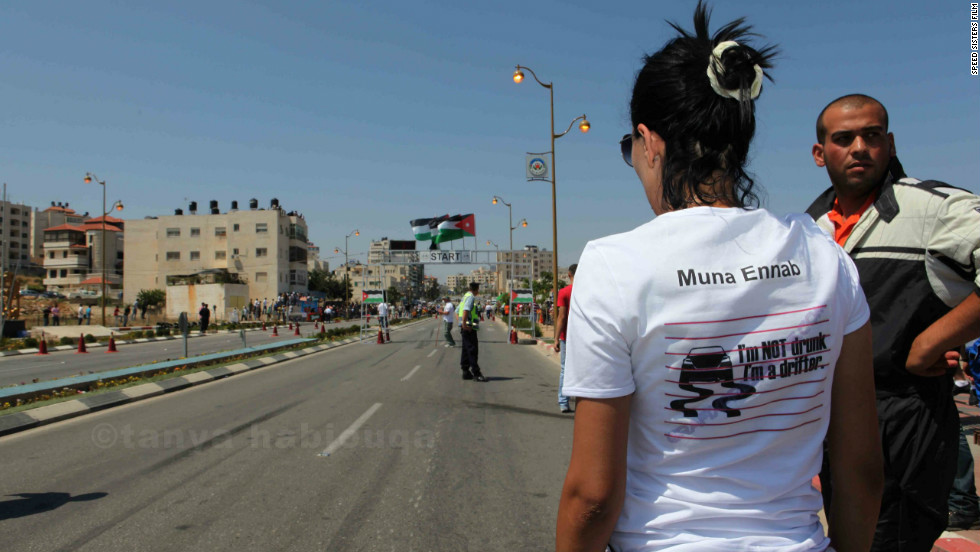 Muna Ennab watches a race in Ramallah. Her t-shirt refers to drift racing, a driving technique in which the driver deliberately oversteers and the rear wheels skid.