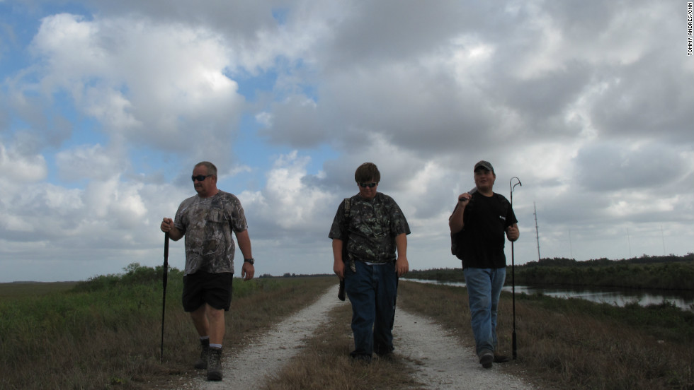 Bob Pawlowski, from left, son Coby and friend Jimmy Harper of Fort Myers, Florida, hike a dirt road in the southeastern portion of the Everglades near Miami. First-time hunters have been directed by the Florida Fish and Wildlife Commission to stay along the levees, a system of roads and canals built in the park to control water flow.