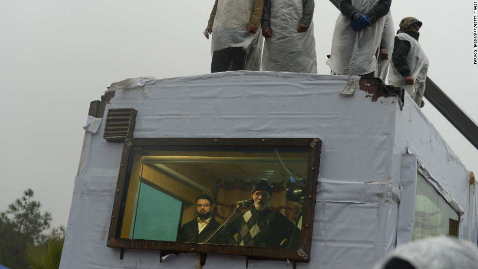 Tahir-ul Qadri (C-below) addresses his supporters from his makeshift room at a protest rally in Islamabad on January 17.