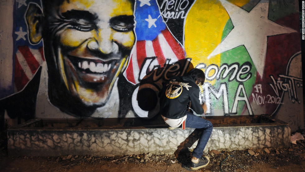MYANMAR: Arkar Kyaw paints graffiti on a wall of Obama in Yangon on November 17, 2012.