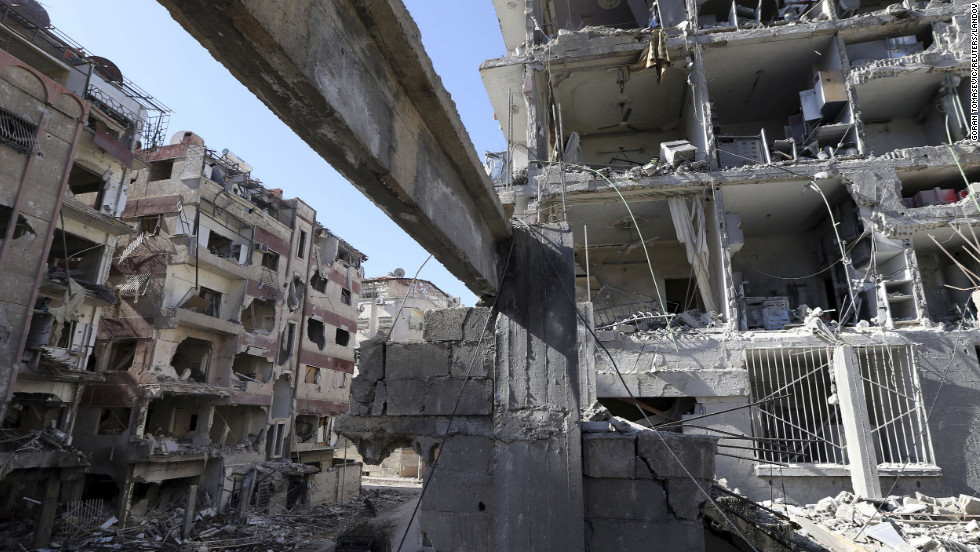 Men pass by buildings destroyed by Syrian air force air strikes in the Duma neighborhood of Damascus on Thursday, January 17.