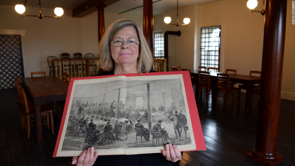 Susan Lemke, a librarian at the National Defense University, holds a depiction of the Lincoln assassination conspirators' trial, while standing in the restored courtroom in Washington where the trial occurred.
