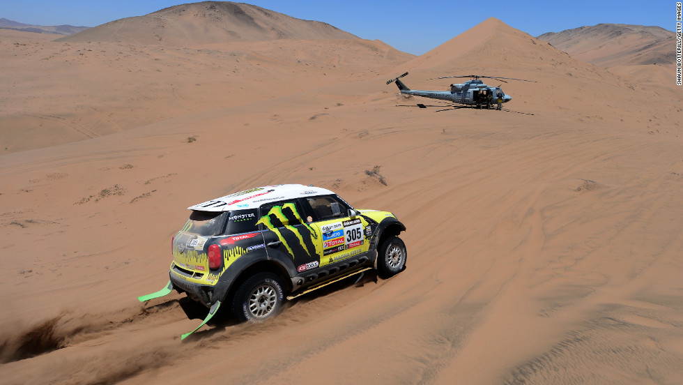 Nani Roma and co-driver Michel Perin of team Mini race through the desert with a helicopter nearby on January 18.