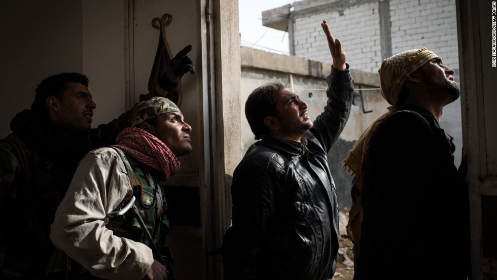Rebel fighters try to locate a government fighter jet in the sky above Aleppo during fighting on January 18.