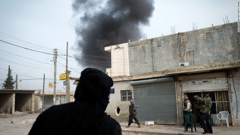 Fighters watch smoke rising from a bombing in Aleppo on January 18.