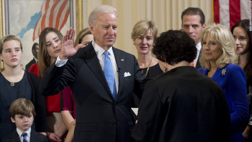 Biden takes the oath of office from U.S. Supreme Court Justice Sonia Sotomayor at the Naval Observatory on Sunday as his wife, Jill Biden, right,  looks on.