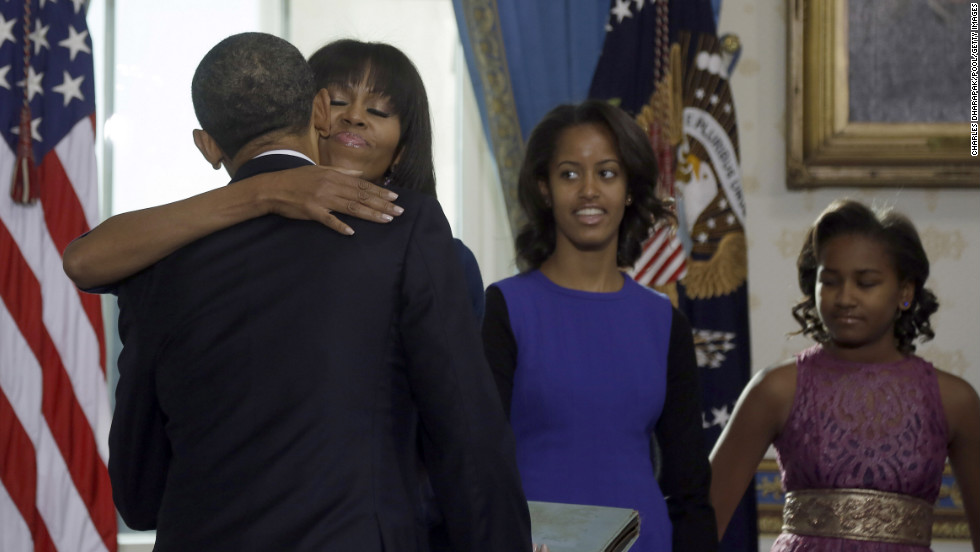 Michelle Obama embraces her husband after he took the oath of office January 20. Daughters Malia, left, and Sasha watch from the side.