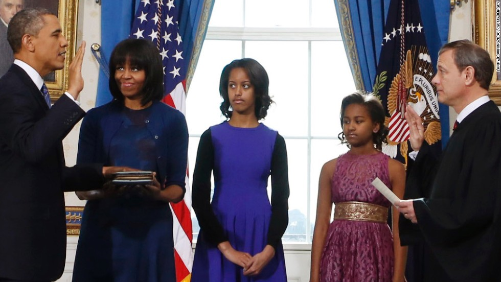 President Barack Obama takes the oath of office Sunday from U.S. Chief Justice John Roberts as first lady Michelle Obama holds the Bible, with daughters Malia, 14, and Sasha, 11, by their parents' side in the White House Blue Room.